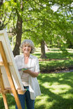 Smiling mature woman painting on canvas in park Stock Image