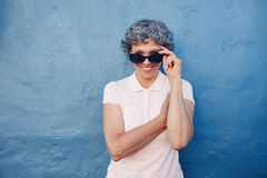 Smiling mature woman peeking over sunglasses. Portrait of smiling mature woman peeking over sunglasses against blue background. Beautiful middle aged female Stock Photos