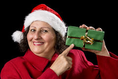 Smiling Mature Woman Pointing at Wrapped Xmas Gift. Female pensioner with a Father Christmas hat is pointing with her right index finger at a gift in her left Stock Images
