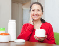 Smiling mature woman puts cream on face Stock Photo