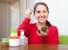 Smiling mature woman  puts mascara on Stock Image