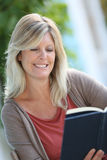 Smiling mature woman reading book Stock Image