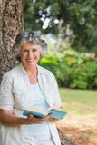Smiling mature woman reading book leaning on tree trunk. Looking at camera at home Stock Photos