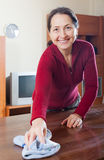 Smiling mature woman in red cleaning  table Royalty Free Stock Photos