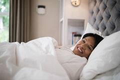 Smiling mature woman resting on bed at home Stock Image