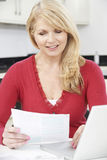 Smiling Mature Woman Reviewing Domestic Finances Stock Image