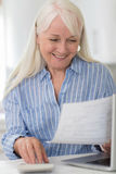 Smiling Mature Woman Reviewing Domestic Finances Stock Photography