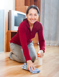 Smiling mature woman rubing parquet floor Royalty Free Stock Photography