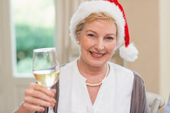 Smiling mature woman in santa hat toasting with white wine Royalty Free Stock Photos