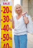 Smiling mature woman  with shopping bag near the banner with sal. E.  Sales, shop, retail, consumer concept Stock Photo