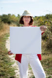 Smiling mature woman showing blank sign for teasing in countryside. Summer outdoors teasing - gorgeous 50s woman with casual hat holding a white blank sign to Stock Image