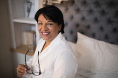 Smiling mature woman sitting on bed at home Stock Images