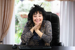 Smiling mature woman sitting at black wooden desk Stock Photos