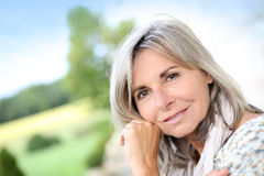 Smiling mature woman sitting in garden Royalty Free Stock Photography