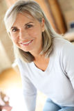 Smiling mature woman sitting at home Royalty Free Stock Image
