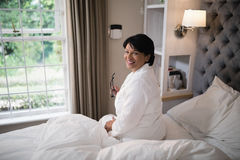 Smiling mature woman sitting in illuminated bedroom at home Stock Images