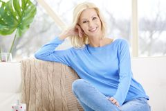 Smiling mature woman sitting on sofa at home royalty free stock photography