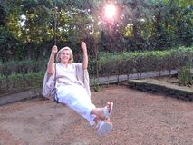 Smiling mature woman sitting on swing stock images