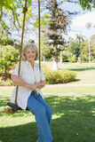 Smiling mature woman sitting on swing in park Royalty Free Stock Image