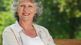 Smiling mature woman sitting on a wooden bench Royalty Free Stock Images