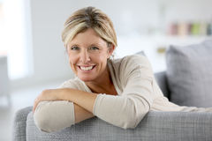Smiling mature woman on sofa Stock Image