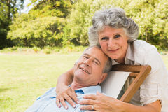 Smiling mature woman standing behind her husband on deck chair Royalty Free Stock Images