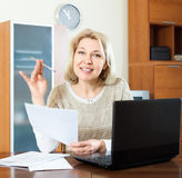 Smiling mature woman staring financial documents Stock Photo