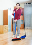 Smiling mature woman sweeping the floor Stock Photography