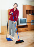 Smiling mature woman sweeping the floor Stock Images