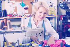 Smiling mature woman tailor using sewing machine Stock Photos