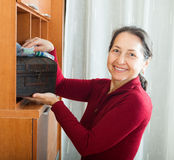 Smiling mature woman wiping the dust Stock Photo