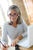 Smiling mature woman working from home. Senior woman at home figuring out income tax Royalty Free Stock Photography