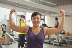 Smiling mature women showing her strength after workout in the gym, arms raised and flexing muscles Royalty Free Stock Photos