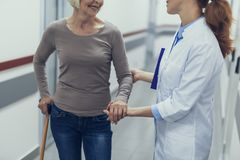 Female doctor is supporting aged lady by hand. Smiling mature women is using cane while visiting hospital. She is standing with therapist in hallway and talking royalty free stock photography