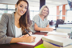 Smiling matures females students writing notes at desk Royalty Free Stock Photos