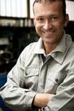 Smiling Mechanic. Close-up of a smiling mechanic inside his auto repair shop Stock Photos
