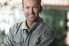 Smiling Mechanic. Close-up of a smiling mechanic inside his auto repair shop Stock Photo