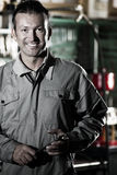 Smiling Mechanic. Close-up of a smiling mechanic inside his auto repair shop Royalty Free Stock Photo