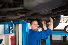 Smiling mechanic adjusting the tire wheel Royalty Free Stock Photos