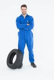 Smiling mechanic with arms crossed standing by tire Royalty Free Stock Photography