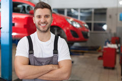 Smiling mechanic in auto repair shop Royalty Free Stock Photography