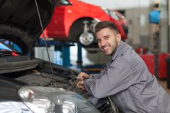 Smiling mechanic at the auto repair shop Royalty Free Stock Photo