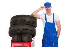 Smiling mechanic buy tires. For the car Royalty Free Stock Photo