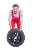 Smiling mechanic and car wheel with black tire Stock Image