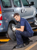 Smiling Mechanic Changing Car Tire. Portrait of smiling mechanic changing car tire at auto repair shop Royalty Free Stock Images