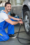 Smiling  mechanic changing tyre on car. Smiling mechanic changing tyre on car wit hydraulic wrench Stock Photography