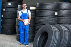 Smiling mechanic checing clipboard car tires. In tire store Royalty Free Stock Photo