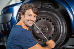 Smiling Mechanic Fixing Car Tire With Rim Wrench Stock Photography