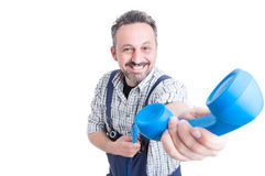 Smiling mechanic giving a blue telephone receiver Royalty Free Stock Photo