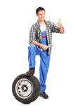 A smiling mechanic giving a thumb up. With a spare tire and wrench  on white background Stock Photo
